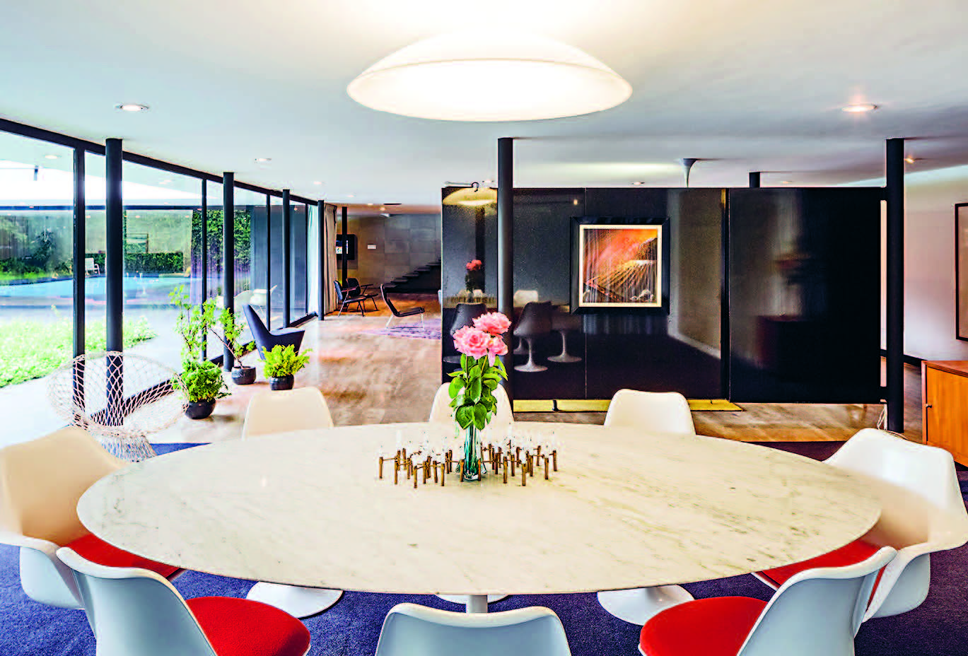 Minimal steel columns full height windows and marble floors are softened thanks to large carpets and drapes
