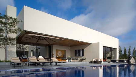 Casa El Arrayàn: vista del fronte della zona giorno segnato da un forte volume sospeso a sbalzo su un setto che definisce la zona porticata, affacciata verso la piscina.
