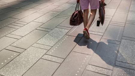 La pavimentazione è stata ridisegnata per facilitare il flusso delle persone: senza ricorrere a segnalazioni o barriere intrusive, la texture delle pietre che rivestono l'asfalto, aiuta i pedoni ad orientarsi. Anche nele ore serali, grazie a piccoli tondini d'acciaio, inseriti nella pavimentazione, che brillano alla luce delle insegne luminose.
