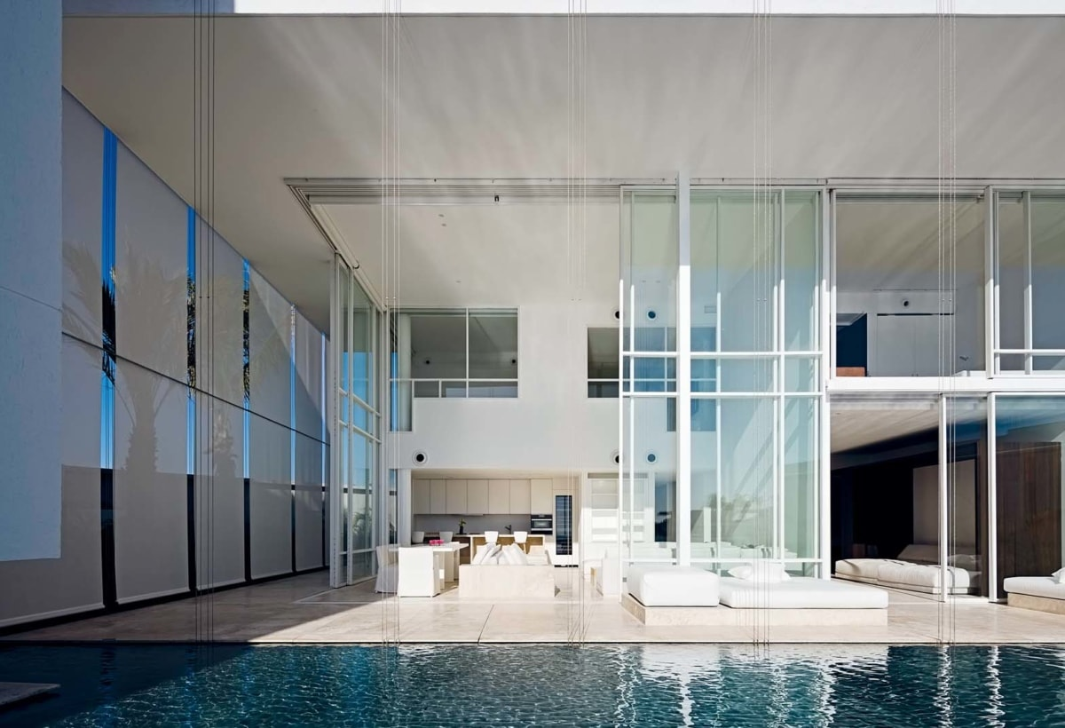 The glass front of a two-story villa open to the reflecting pool and projected towards the horizon of the ocean. The full-height windows can be screened by external roller blinds.